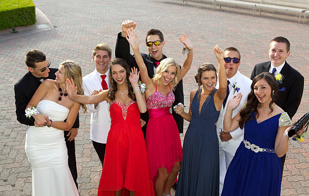 group of teenagers at the prom  having fun posing outdoors - prom stock photos and pictures