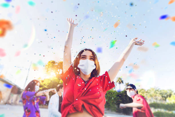 Group of teenagers celebrating at a party wearing face masks stock photo