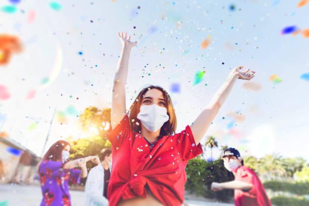 gruppe von teenagern feiern auf einer party mit gesichtsmasken - party stock-fotos und bilder