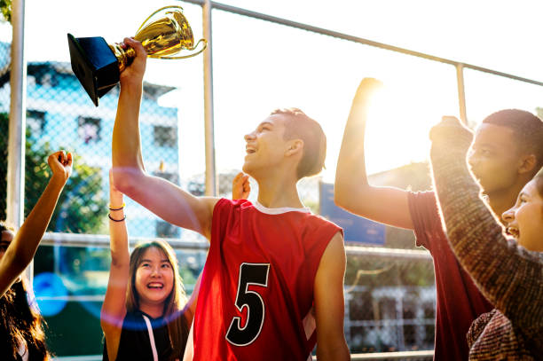 Group of teenagers cheering with trophy victory and teamwork concept stock photo