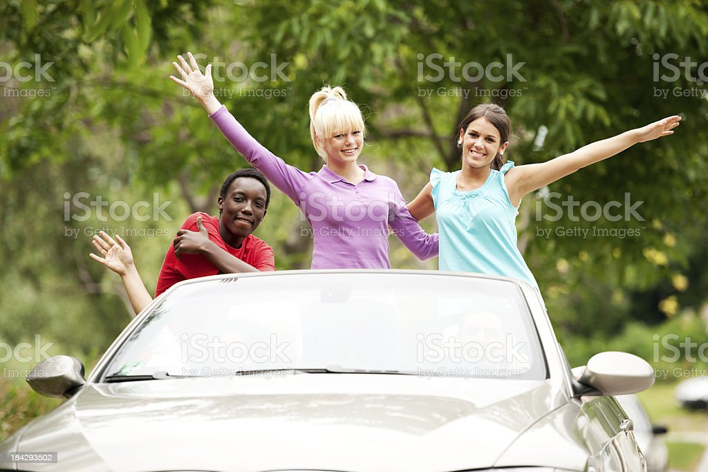 Group of teenagers driving a Convertible car. royalty-free stock photo