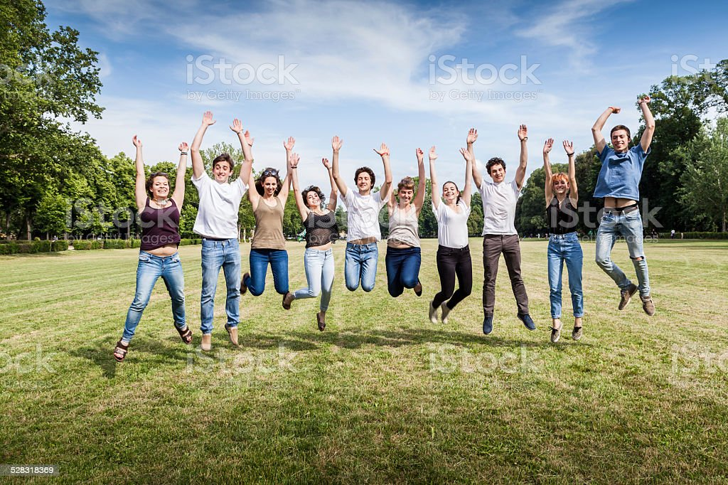 Group of teenagers jumping in the park stock photo