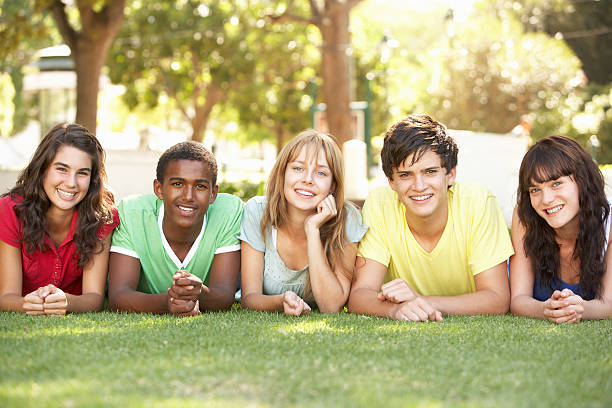 Group Of Teenagers Lying On Stomachs In Park  teenagers only stock pictures, royalty-free photos & images