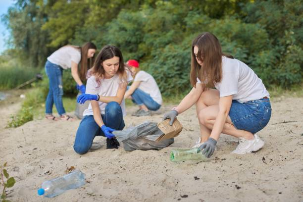 Grupo de adolescentes en la orilla del río recogiendo basura plástica en bolsas - foto de stock