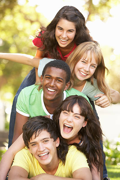 Group Of Teenagers Piled Up In Park Group Of Teenagers Having fun Piled Up In Park teenagers only stock pictures, royalty-free photos & images