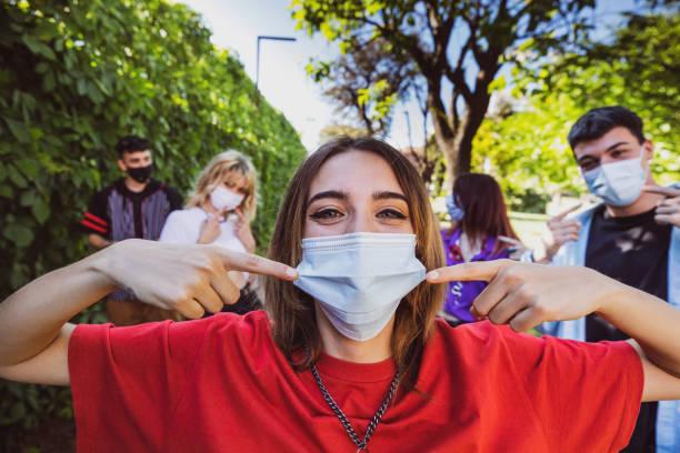 gruppe von teenagern posiert mit ihren schützenden gesichtsmasken - jugendalter stock-fotos und bilder
