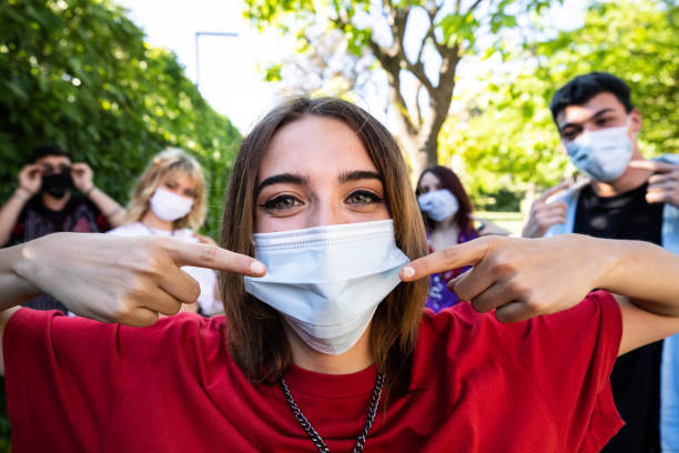 Group of teenagers posing showing their protective face masks stock photo
