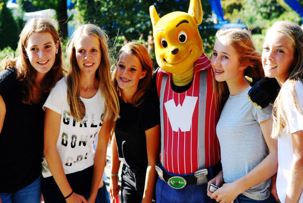 groupe d'adolescents posant avec une mascotte. - mascotte photos et images de collection