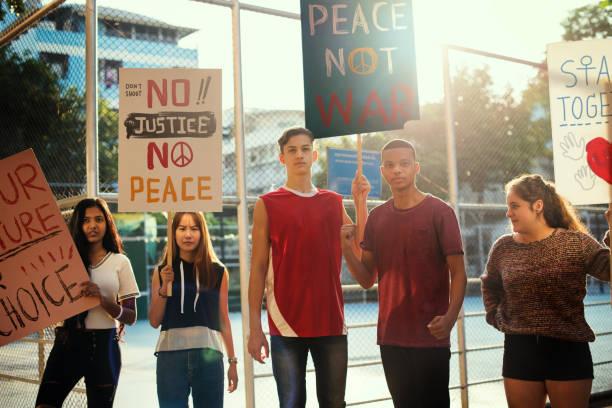 gruppe von jugendlichen protest demo halten plakate antikriegs gerechtigkeit frieden konzept - britische politik stock-fotos und bilder