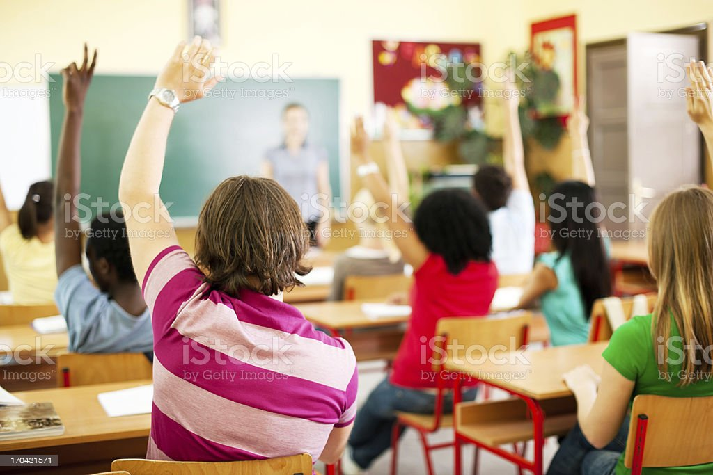 Group of teenagers sitting in the classroom with raised hands. royalty-free stock photo