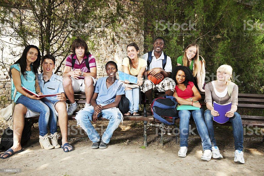 Gruppe von Teenagern, die auf Bank im Freien – Foto