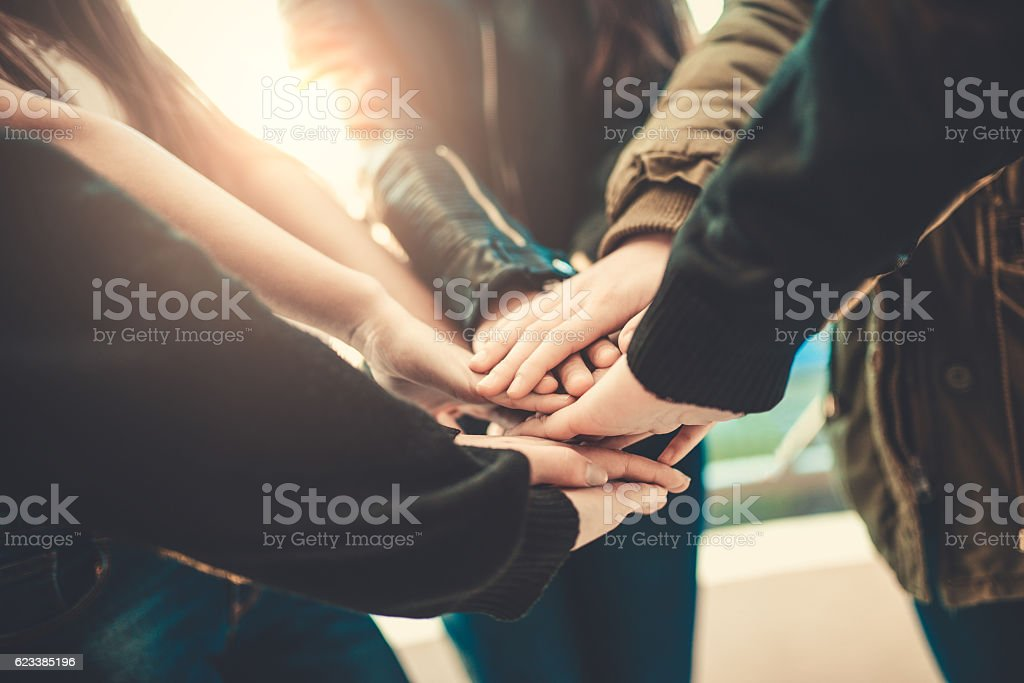 Group of Teenagers Volunteer Holding Hands in Circle for Teamwork stock photo