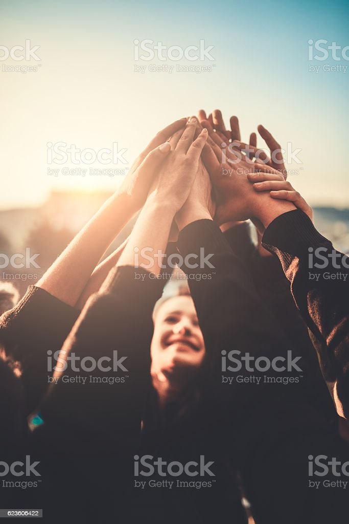 Group of Teenagers Volunteer with Raised Hands to the Sky stock photo