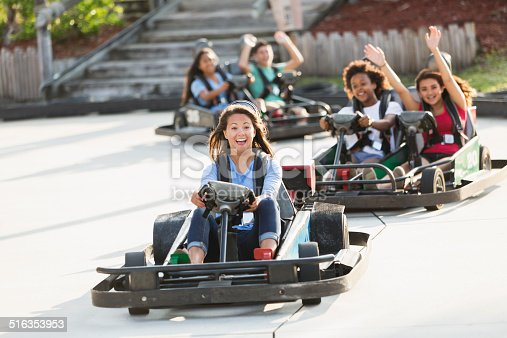 Multi-ethnic group of teens (16 to 18 years) riding go carts at amusement park.  Focus girl in front.