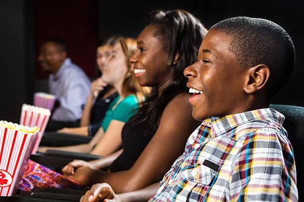gruppe der teenager beobachten film zusammen in örtlichen kino - jugendfilm stock-fotos und bilder