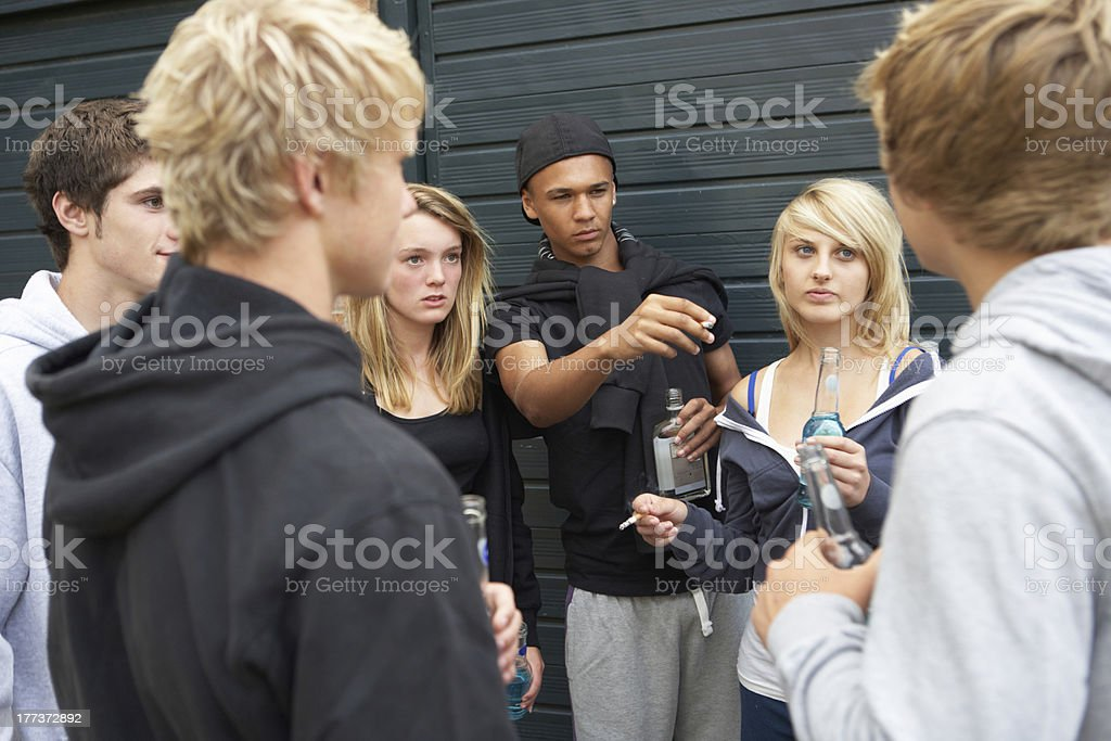 Group Of Threatening Teenagers Hanging Out Together Outside Drinking stock photo
