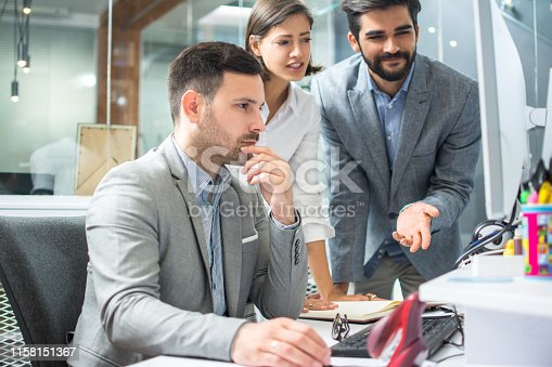 Group of three business people discussing project on computer screen at office.