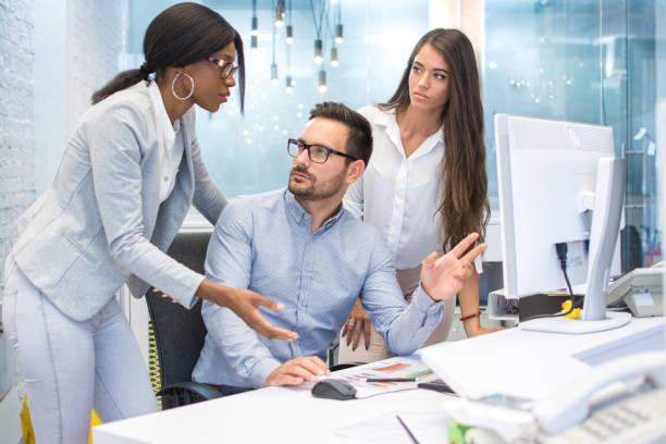 Gruppe von drei Geschäftsleute diskutieren einige Dokumente auf Desktop-Computer im modernen Büro. – Foto