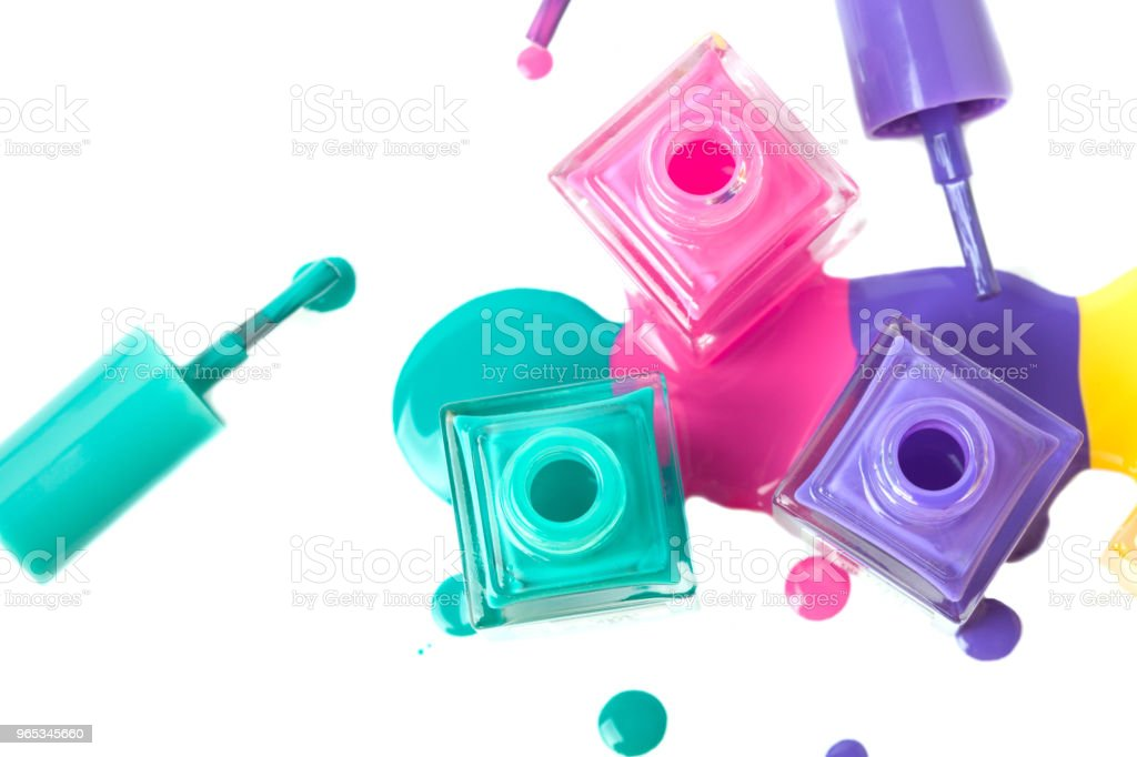 group of three colorful nail polish bottles on spilled paint royalty-free stock photo