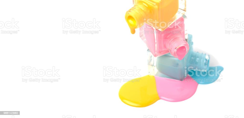 group of three colorful nail polish bottles on spilled paint - Royalty-free Beauty Stock Photo