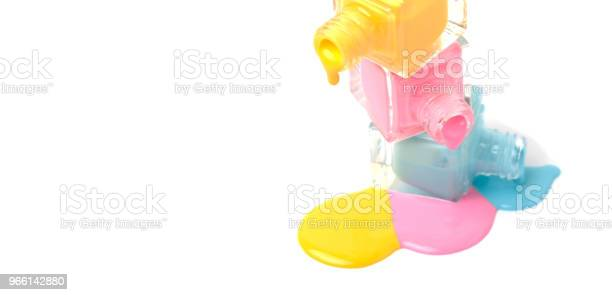 Group Of Three Colorful Nail Polish Bottles On Spilled Paint Stock Photo - Download Image Now