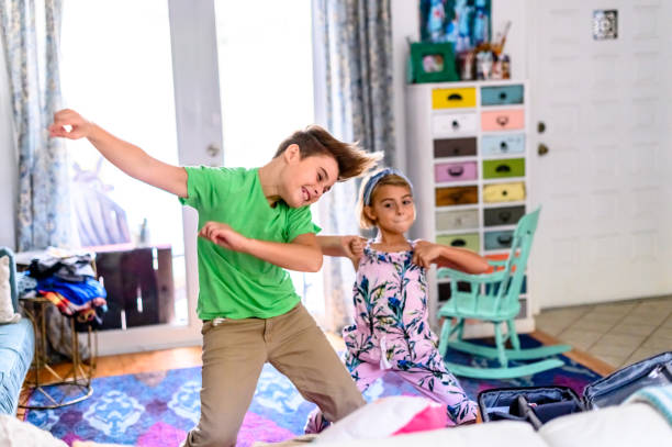 Group of three elementary age siblings have a dance party in the living room at home with energy stock photo
