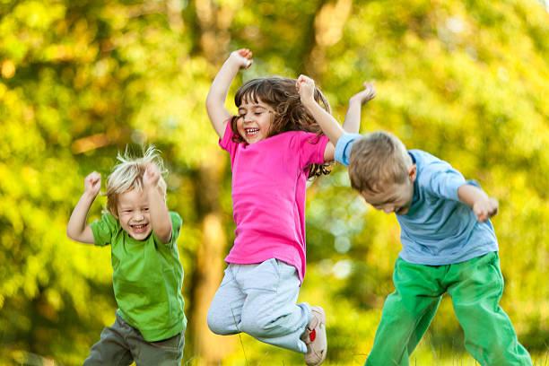 gruppe von drei glückliche kinder springen im freien - kinder picknick spiele stock-fotos und bilder