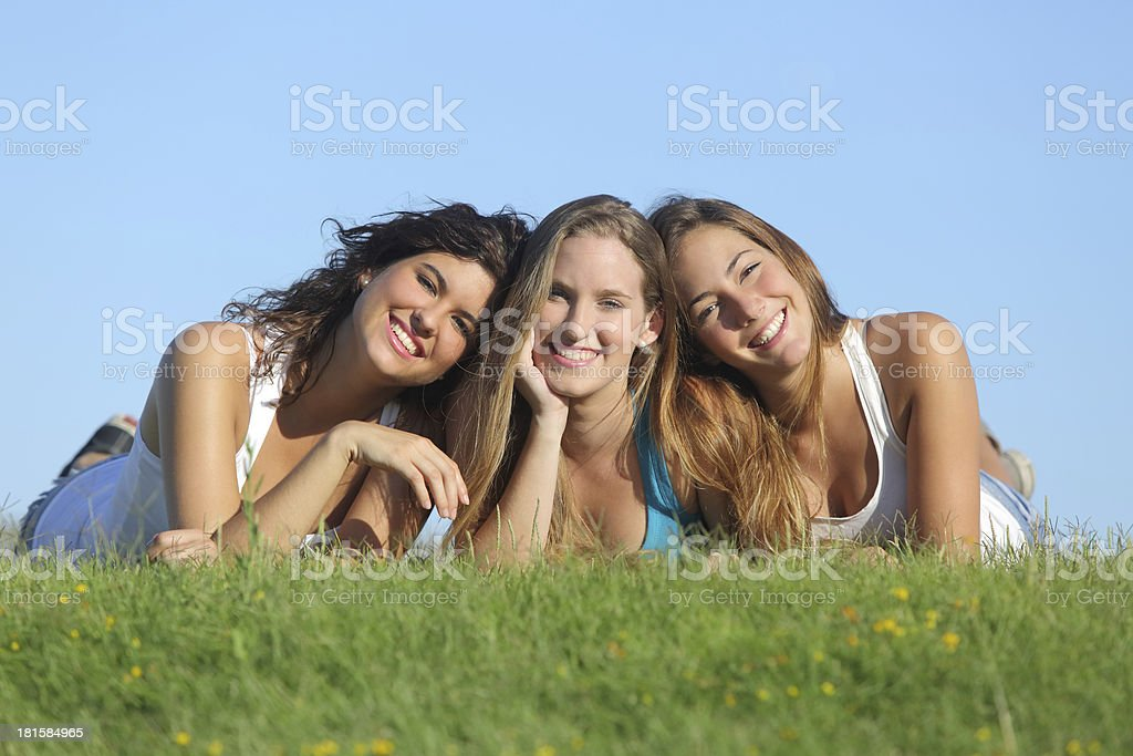 Group of three happy teenager girls lying on the grass royalty-free stock photo