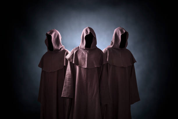 Group of three scary figures in hooded cloaks stock photo