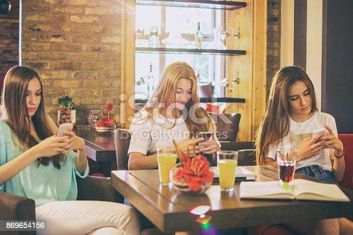 istock Group of three teenage girls using smart phones at cafe. 869654156