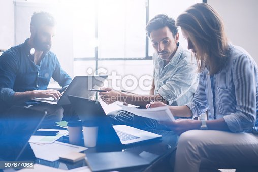 istock Group of three young coworkers working together in modern coworking studio.Woman pointing on paper document and talking with partners about new startup project.Horizontal,blurred background. 907677068