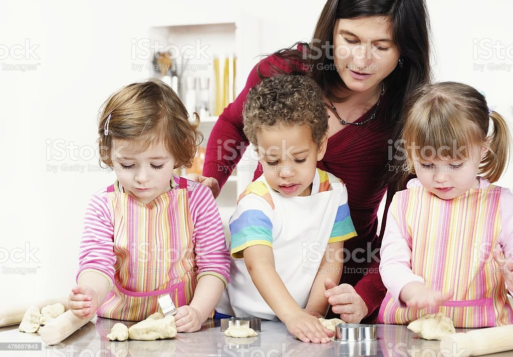 Group Of Toddlers/ Children Preparing Dough With Their Carer/ Teacher stock photo