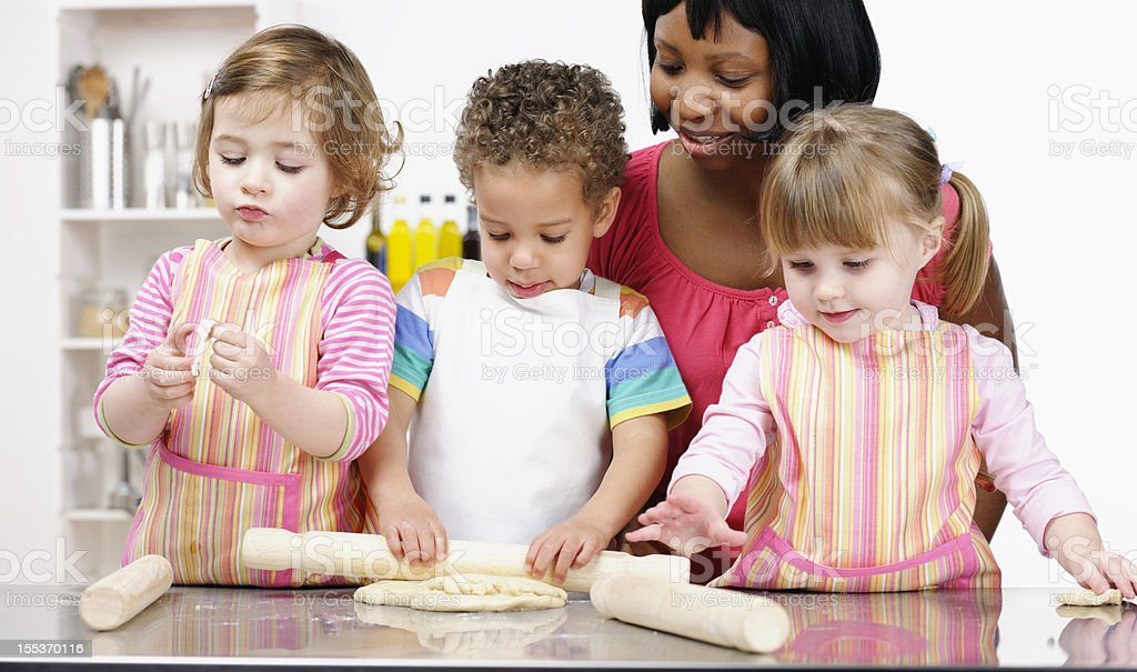 Group Of Toddlers/ Little Children Being Supervised While Preparing Dough royalty-free stock photo