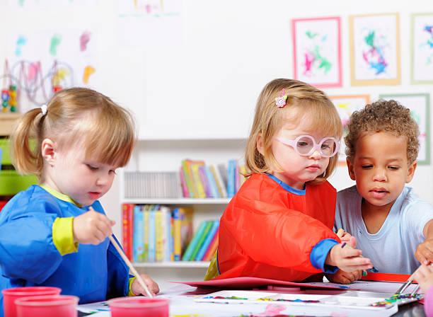 Gruppe von Babys Malerei In ein Kinderzimmer Ambiente – Foto