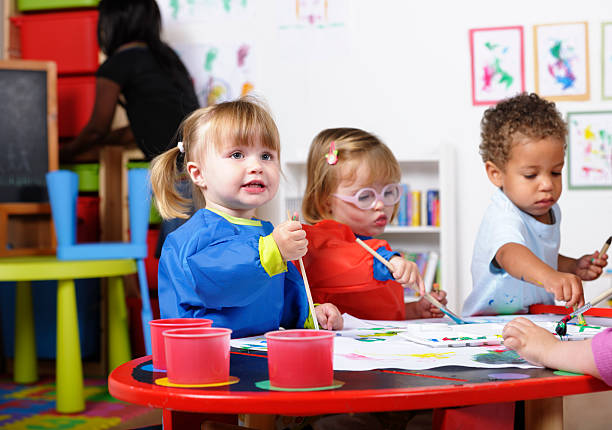 Group Of Toddlers Painting While Their Carer Tidies stock photo