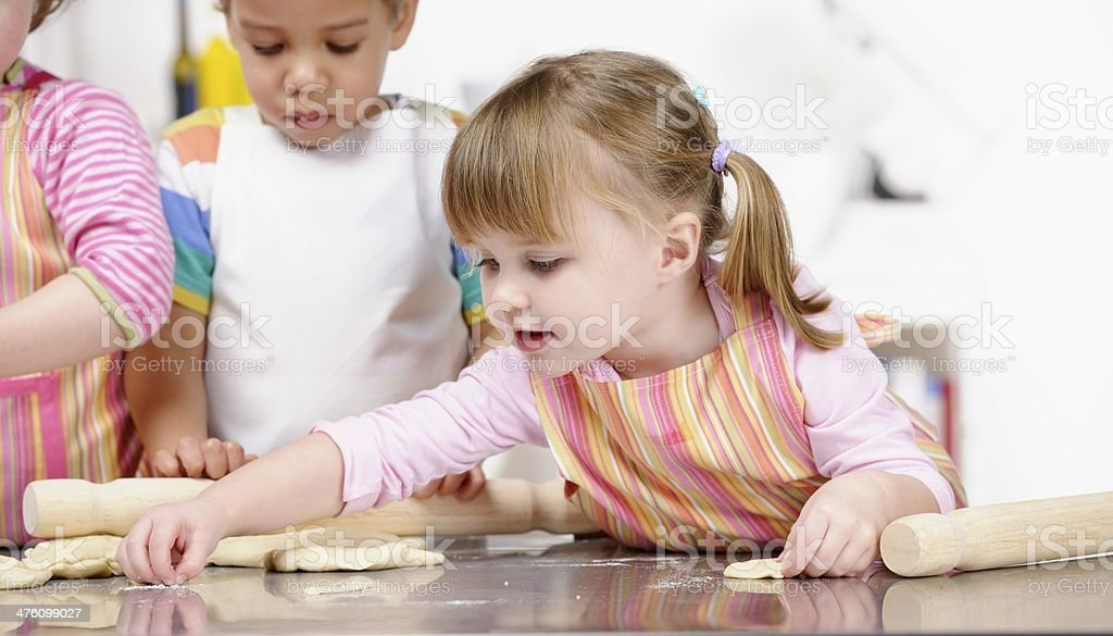 Group Of Toddlers/Children Preparing Dough/ Baking In The Kitchen stock photo
