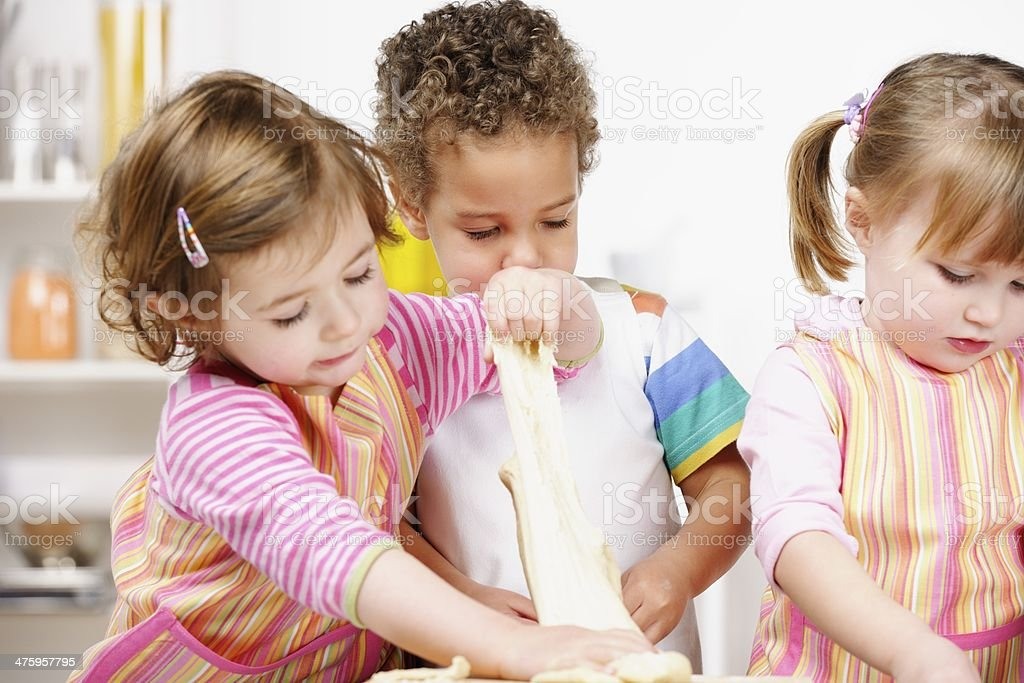 Group Of Toddlers/Children Preparing Dough  In The Kitchen stock photo