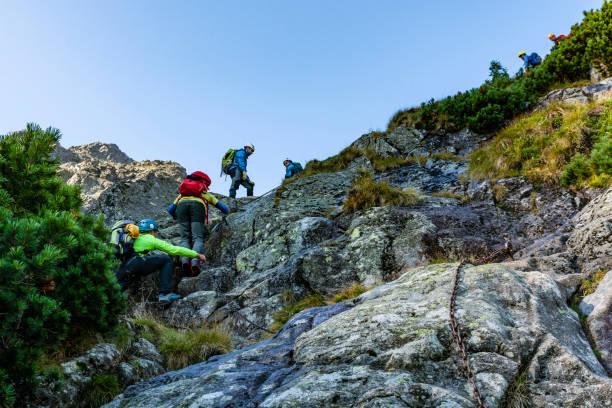 Eine Gruppe von Touristen erklimmt eine felsige Straße in den Bergen, die zusätzlich mit Ketten versichert ist. – Foto