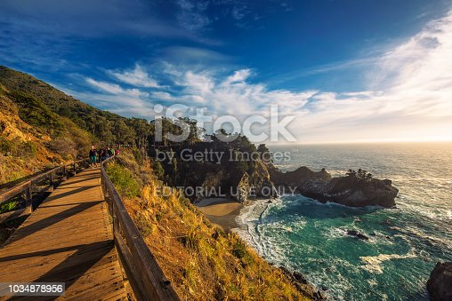 Big Sur, California, USA - January 7, 2018 : Group of tourists coming to the McWay Falls in Big Sur state park, California.