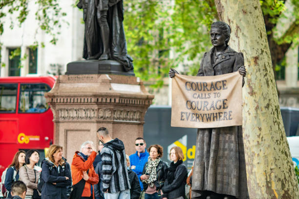Group of tourists gather by the newly erected statue of Millicent Fawcett in Parliament Square, London, UK, She campaigned for women's right to vote during the early 20th Century and is seen as one of the most influential feminists of the past 100 years. 3rd May, 2019 - Group of tourists gather by the newly erected statue of Millicent Fawcett in Parliament Square, London, UK, She campaigned for women's right to vote during the early 20th Century and is seen as one of the most influential feminists of the past 100 years. suffragist stock pictures, royalty-free photos & images