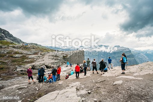 Odda, Norway - August 4, 2014: Group Of Unrecognizable Tourists People On The Top Of The Norwegian Mountains Trolltunga. Troll's Tongue Rock Above Lake Ringedalsvatnet, Norway