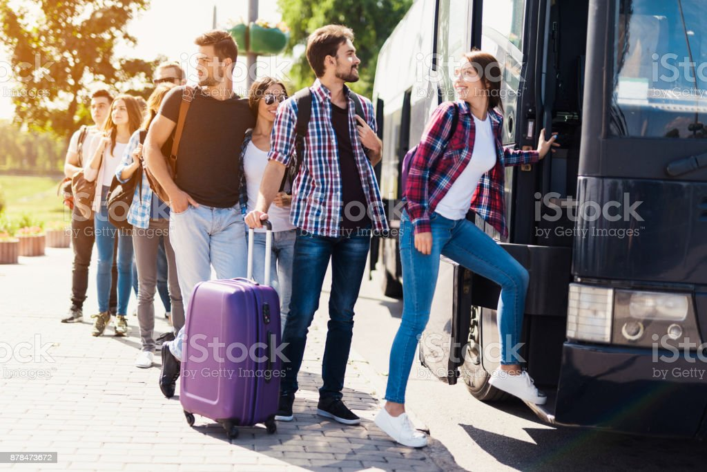 A group of tourists preparing to get on the bus. The guy with the girl goes into the bus and brings in their luggage. stock photo