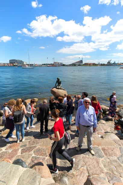 gruppe von touristen, die fotos von der kleinen meerjungfrau, kopenhagen, dänemark machen - kleine meerjungfrau kunst stock-fotos und bilder