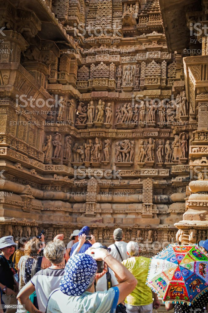 A group of tourists taking picture of the Kama Sutra carvings at Lakshmana Temple in the Western Group of Temples stock photo