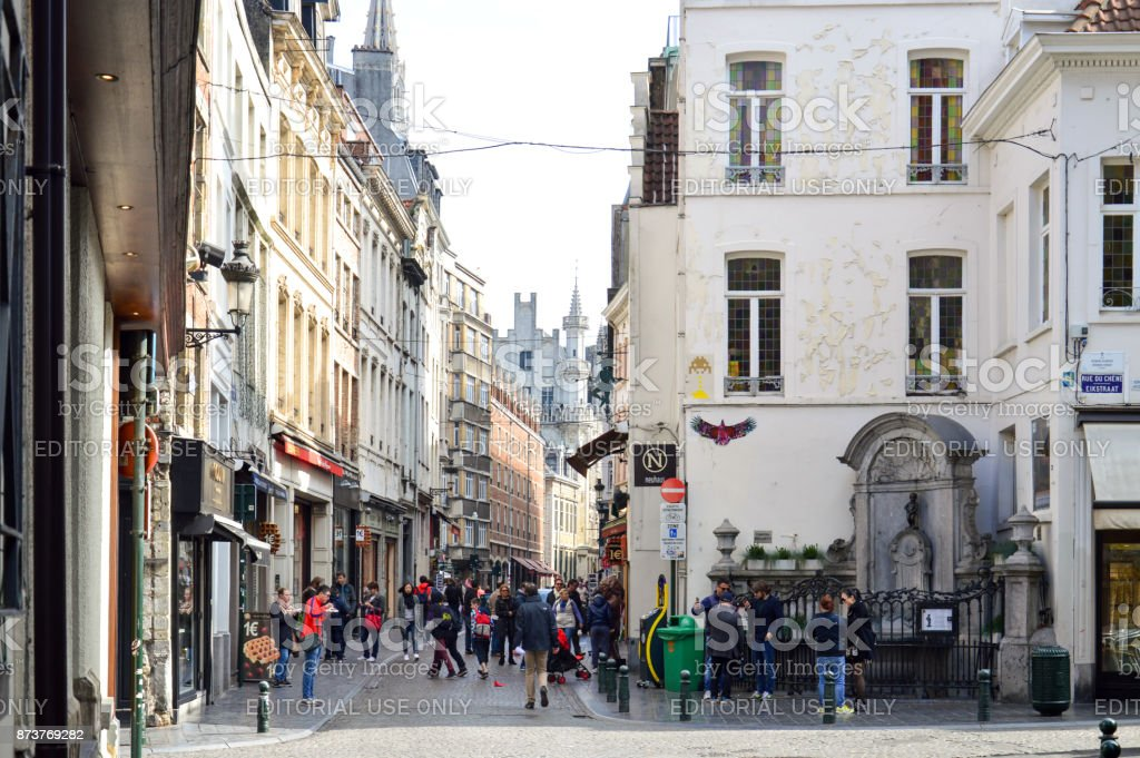 Group of tourists visiting Manneken Pis or Little Man Pee, a landmark small bronze sculpture designed by Hiëronymus Duquesnoy the Elder, located near Grand Place in the city of Brussels, Belgium stock photo