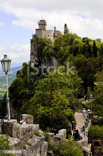 San Marino, Italy, 09 May, 2019: group of tourists walking across old stone bridge towards the Fortress Guaita on Mount Titano, most famous tower of San Marino with foliage top view