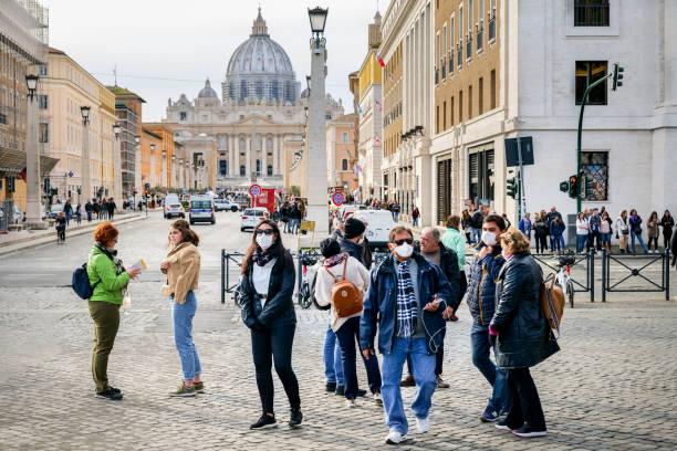 Un groupe de touristes avec des masques médicaux sur leurs bouches sur la place Saint-Pierre - Photo
