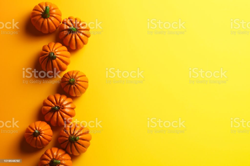Group Of Toy Pumpkins On Yellow Background stock photo