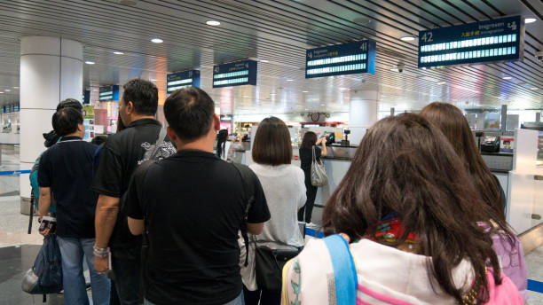 MALAYSIA - MAR 21, 2017: Group of travelers enter immigration control at Kuala Lumpur International Airport (KLIA) in Malaysia. MALAYSIA - MAR 21, 2017: Group of travelers enter immigration control at Kuala Lumpur International Airport (KLIA) in Malaysia. pasport malaysia stock pictures, royalty-free photos & images