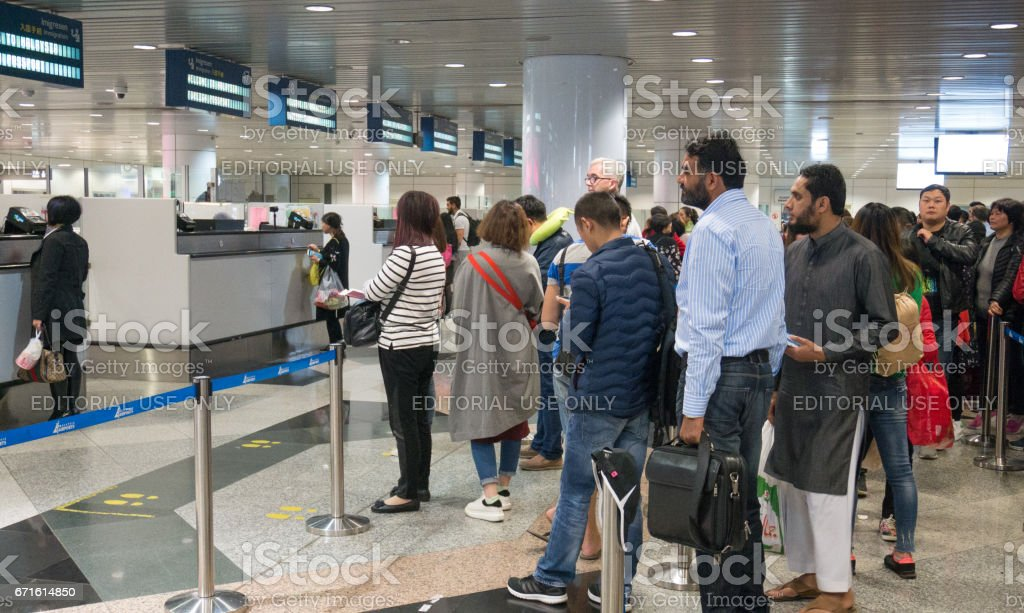 MALAYSIA - MAR 21, 2017: Group of travelers enter immigration control at Kuala Lumpur International Airport (KLIA) in Malaysia. stock photo